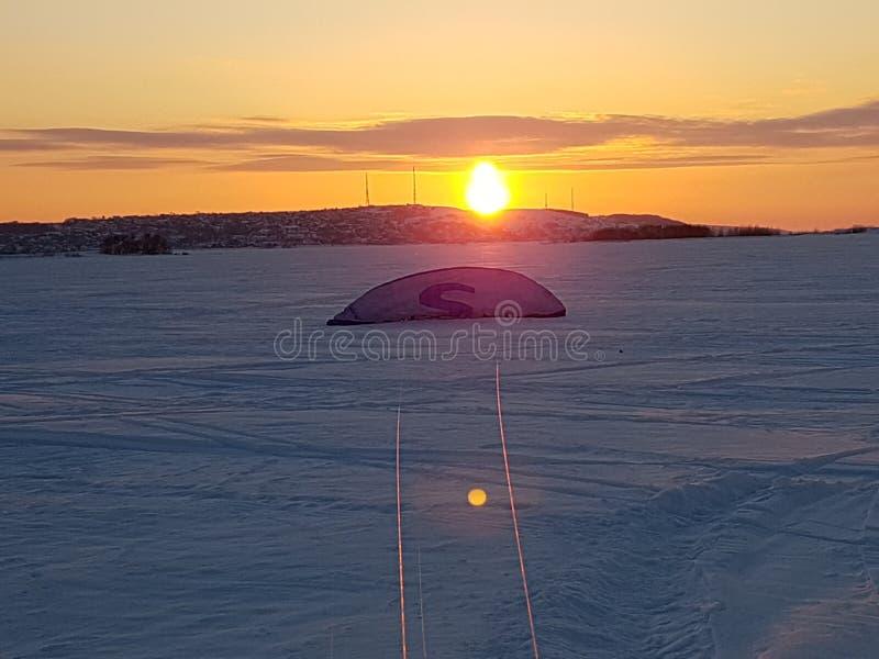 Övervintra solnedgången, solen, bakgrunden, landskapet som kitesurfing, draken, draken, staden, längdlöpning, guling, blått, ljus arkivbild