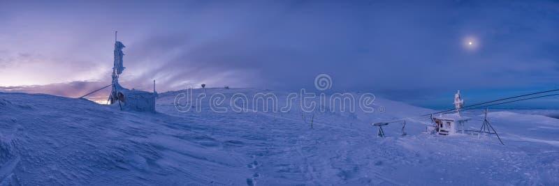 Övervintra solnedgångsnöfältet överst av berget under färgrik himmel royaltyfria bilder