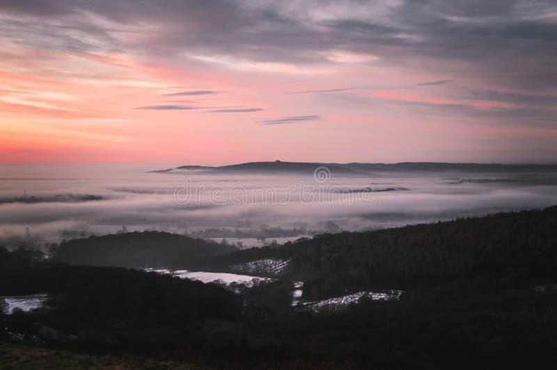 Övervintra soluppgång från de Malvern kullarna, och mist täcker bygden över Gloucestershire, England arkivbild