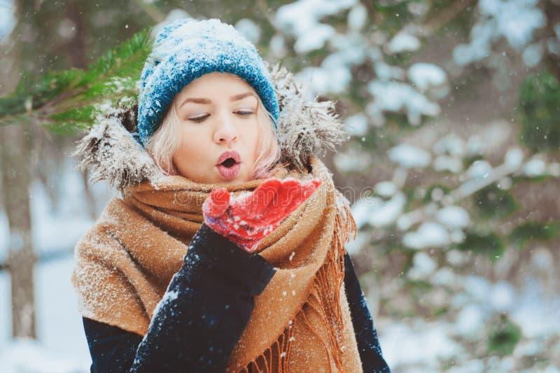 övervintra ståenden av den lyckliga unga kvinnan som går i snöig skog i varm dräkt som blåser snö under snöfall royaltyfri fotografi