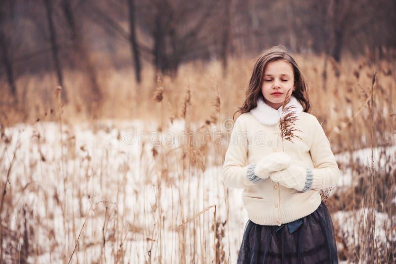 Övervintra ståenden av den romantiska barnflickan på gå i snöig skog royaltyfri fotografi