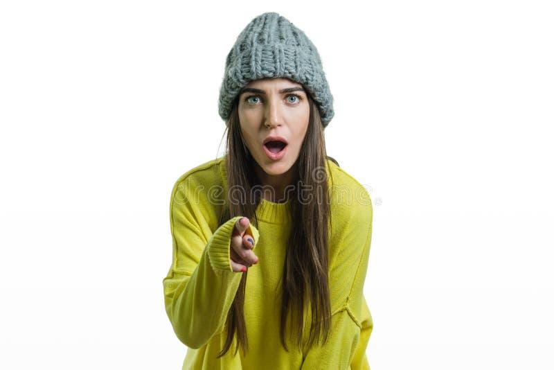 Övervintra ståenden av en emotionell flicka i den gula tröjan och en luva, isolerad vit bakgrund, kvinnavisningpekfinger till arkivbild
