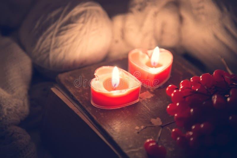 Övervintra stilleben med bär för en rönn, den stack tröjan och två röda stearinljus på en gammal bok som ett symbol av förälskels arkivbilder