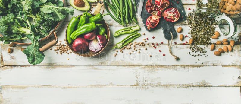 Övervintra vegetariska matmatlagningingredienser över vit bakgrund, vertikal sammansättning royaltyfria bilder