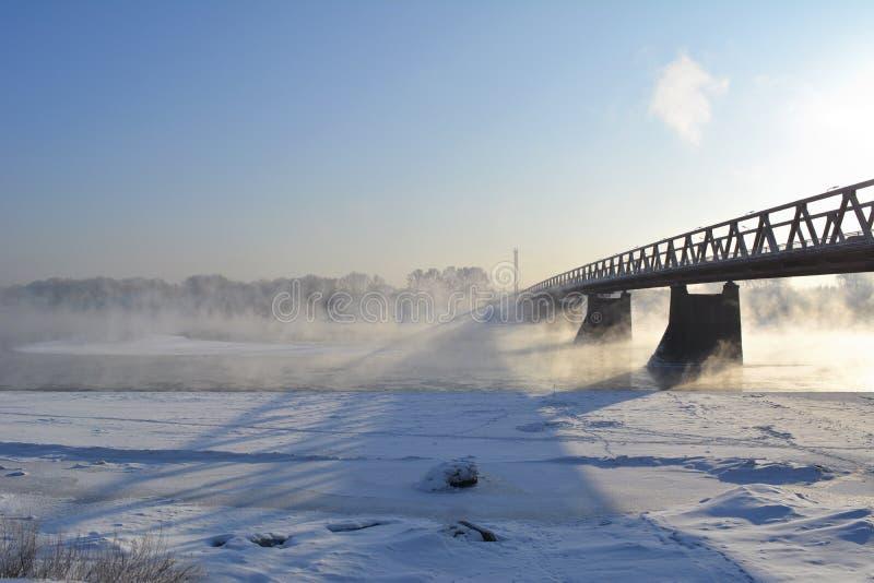 övervintrar trees för snow för sky för lies för frost för mörk dag för bluefilialer Landskapet med bron över floden, det fryser i arkivbild