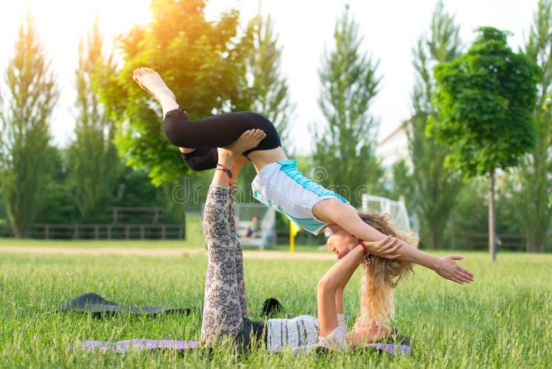 Övning av acroyogaen i natur med två flickor royaltyfri foto