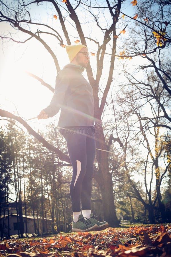 Övning för ung man med hopprepet på naturen royaltyfri foto