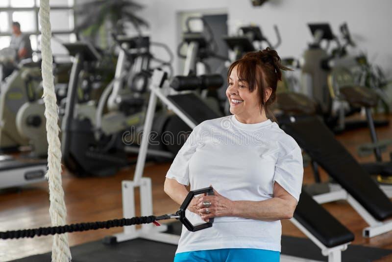 Övningar för äldre kvinna i modern idrottshall arkivbild