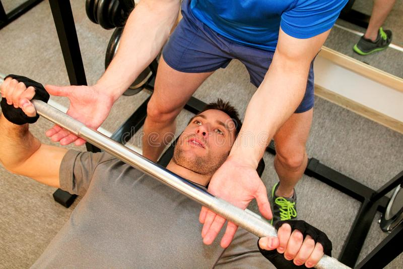 Övningar för brösten med skivstången i idrottshallen royaltyfria foton