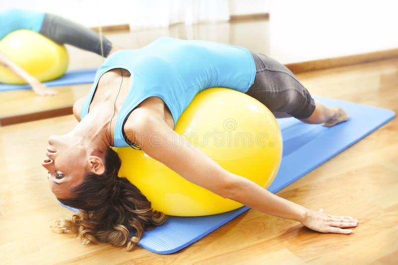 Övningar för kvinnadanandekropp på en gul boll royaltyfri fotografi