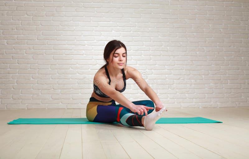 Övningar för yoga och för kondition för kvinnagenomkörare som inomhus sträcker kroppen royaltyfria foton