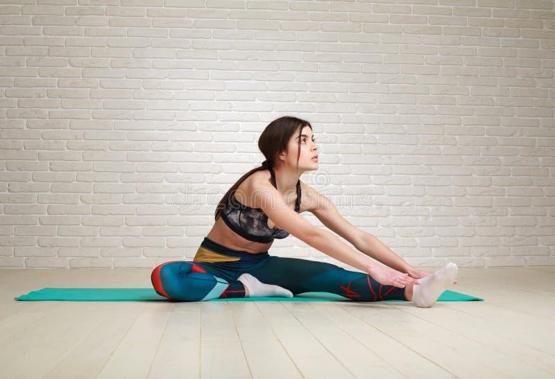 Övningar för yoga och för kondition för kvinnagenomkörare som inomhus sträcker kroppen royaltyfri fotografi