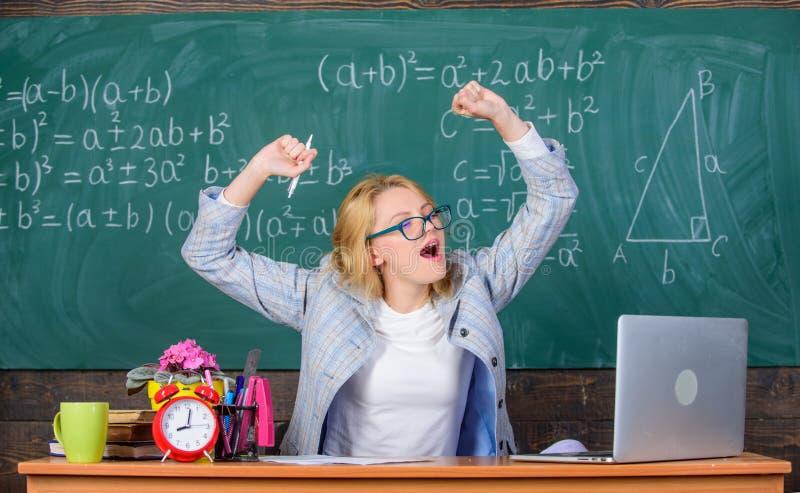 Övningar som underhåller livlighet Lärarekvinnan sitter bakgrund för den svart tavlan för tabellklassrumet Faktisk skola för arbe fotografering för bildbyråer