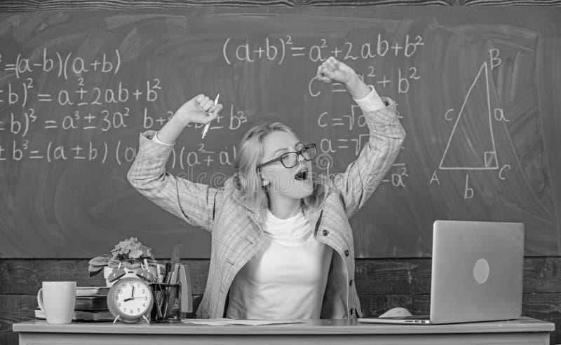 Övningar som underhåller livlighet Lärarekvinnan sitter bakgrund för den svart tavlan för tabellklassrumet Faktisk skola för arbe royaltyfri fotografi