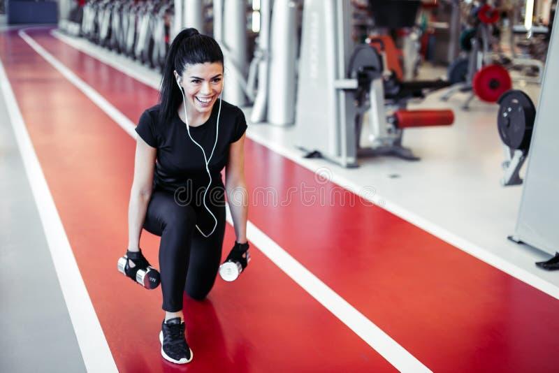Övningen för genomköraren för hantelutfallkvinnan, en bensplittring squats royaltyfri fotografi