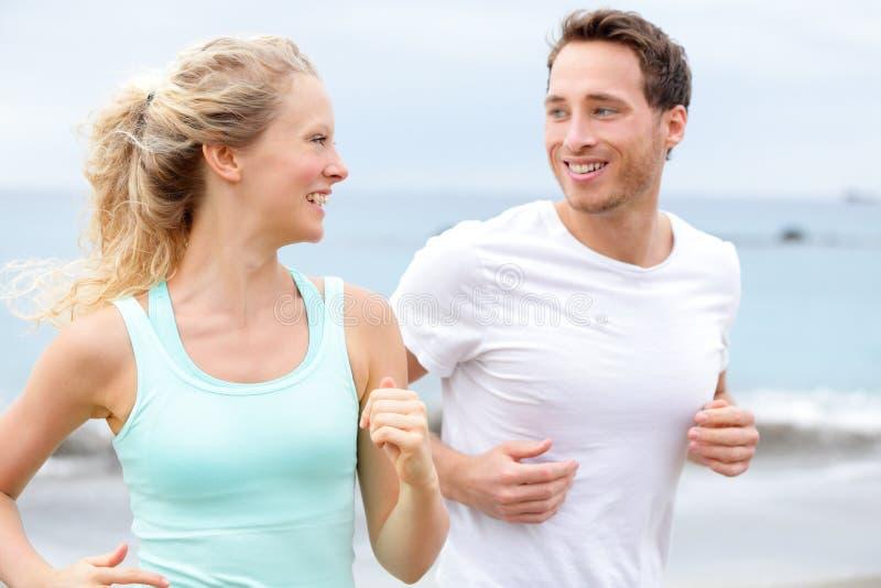 Övningsspringpar som joggar på strandsamtal royaltyfria foton