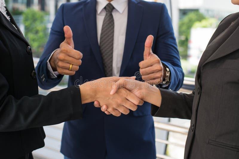Övre affärsmanshowtumme och affärskvinna som skakar händer för demonstrering av deras överenskommelse att underteckna överenskomm arkivbild