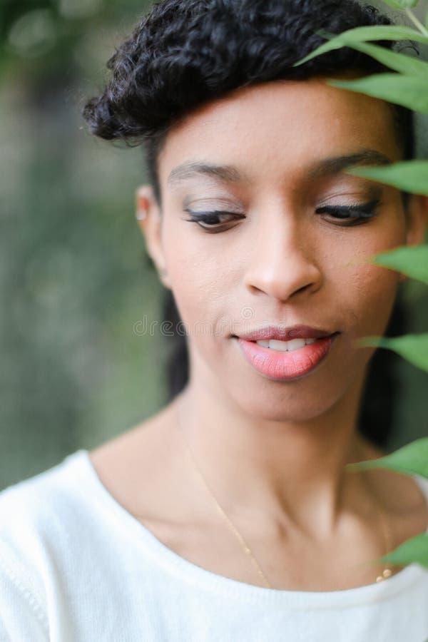 Övre framsida för slut av den svarta afro amerikanska flickan som håller det gröna bladet och att ha blusen för smällar och för b arkivbild