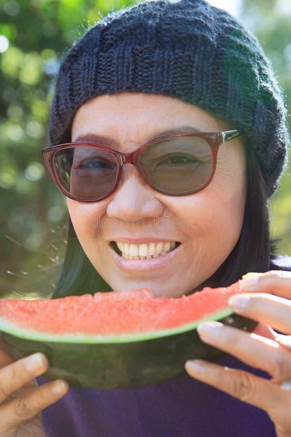 Övre framsida för slut av den unga kvinnan med att äta vattenmelonbruk för goda royaltyfria foton