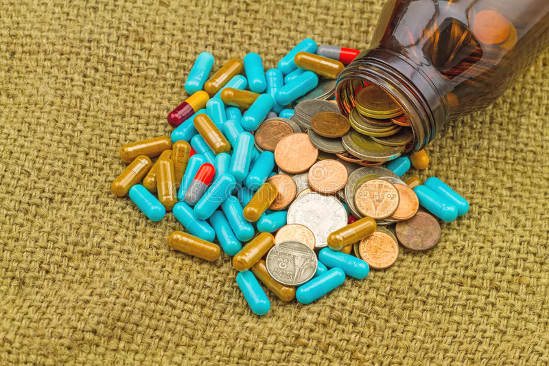 Övre hög för slut av medicin i brun flask- och myntbunt på sa arkivfoton