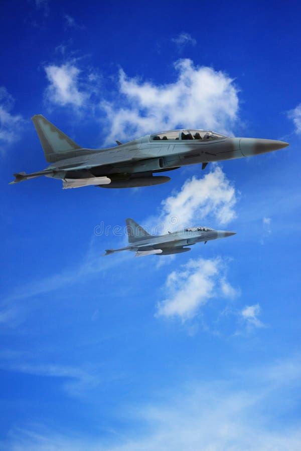 Övre sikt av det militära jetflyget över skyen arkivfoton