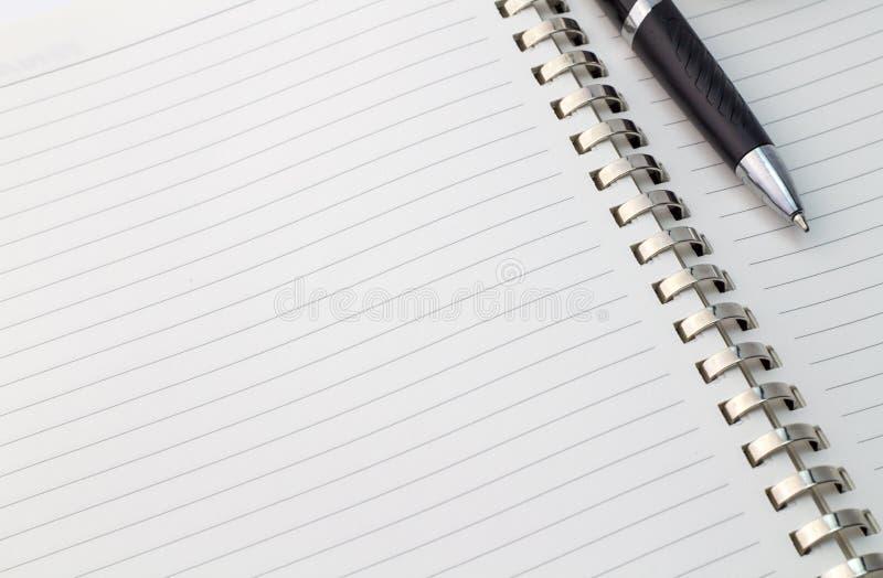 Övre sikt för slut av anmärkningsboken med silvermetalllimbindningen och pennan med royaltyfri bild