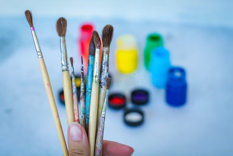 Övre sikt för slut av den kvinnliga handen med uppsättningen av målarfärgborstar på blå suddig bakgrund med målarfärgcans royaltyfri fotografi