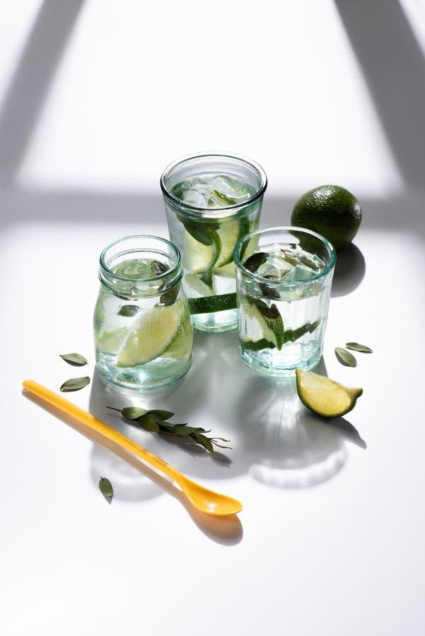 övre sikt för slut av den plast- skeden, exponeringsglas med vatten, limefruktstycken och iskuber royaltyfria foton