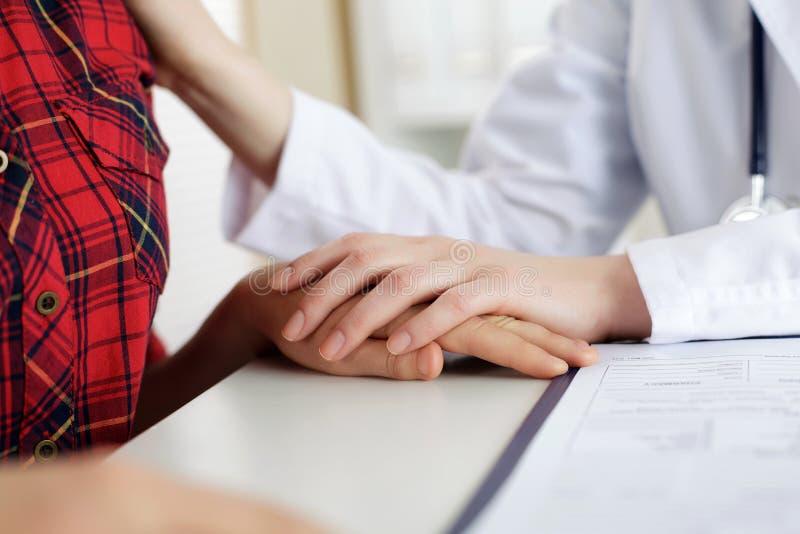 Övre sikt för slut av den rörande tålmodiga handen för kvinnlig doktor för encoura royaltyfri bild