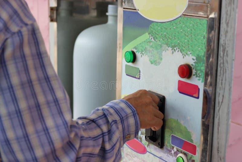 Övre sikt för slut av handen av det mänskliga insättande myntet in till den gamla varuautomaten för påfyllning en plast- vattenfl royaltyfria bilder