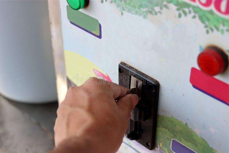 Övre sikt för slut av handen av det mänskliga insättande myntet in till den gamla varuautomaten, grunt djup av fältet, automat royaltyfri bild