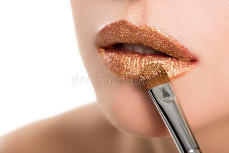 Övre sikt för slut av kvinnan som applicerar guld- läppstift med makeupborsten arkivbild