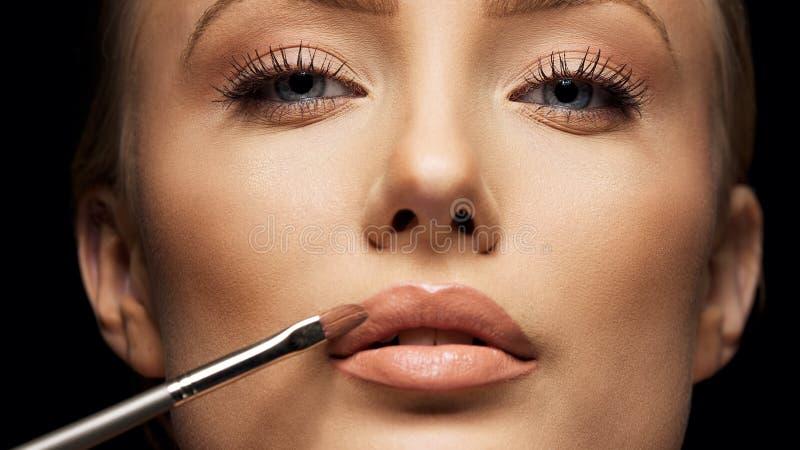 Övre skörd för slut av den kvinnliga framsidan som applicerar smink royaltyfri bild