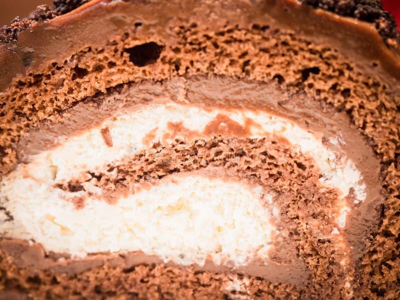 Övre texturlager för slut från stycke av serven för chokladkaka i whi royaltyfri bild