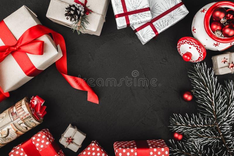 Övrebästa sikt av ett rött band, julklappar, trädleksaker och en vintergrön filial på en stensvartbakgrund royaltyfria bilder