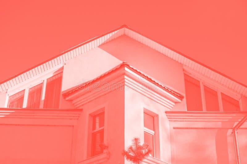 Övredel av fasaden av detberättelse huset med att slutta taket mot den blåa himlen tonad korallfärg fotografering för bildbyråer