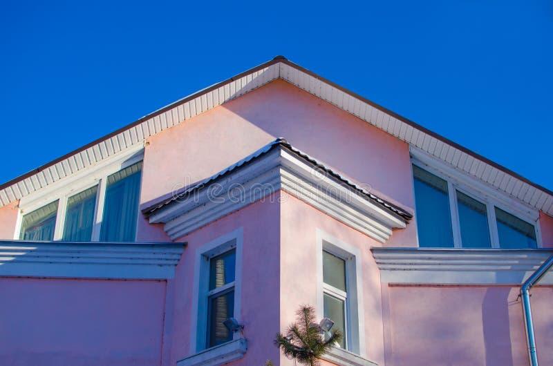 Övredel av fasaden av detberättelse huset av rosa färg med att slutta taket mot den blåa himlen arkivfoton