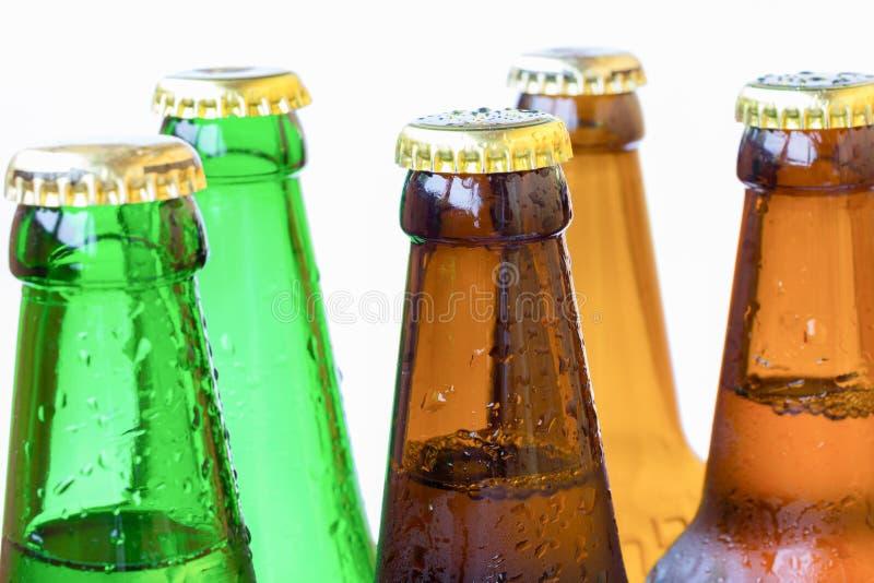 Övredel av flaskor av kulört exponeringsglas med droppar av vatten royaltyfria foton