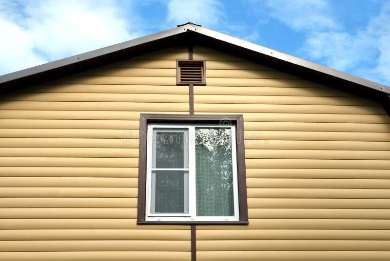Övregolvet av den lantliga husväggen som täckas med den gula sidingen och brun metall, taklägger främre sikt arkivbild