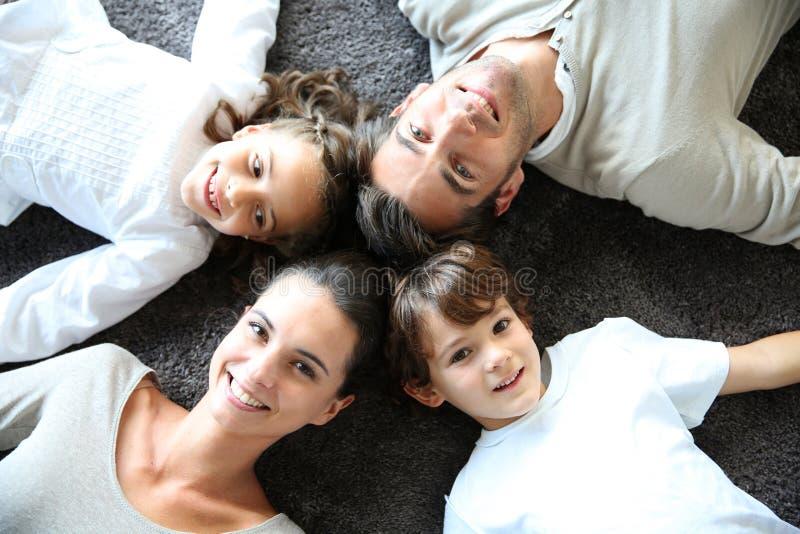 Övresikt av den lyckliga familjen som ligger på matta arkivfoton