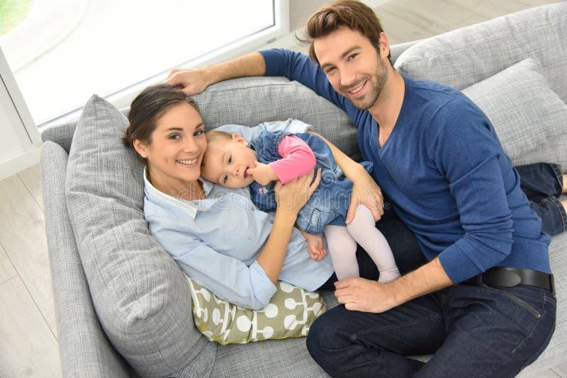 Övresikt av den lyckliga unga familjen som ligger på soffan arkivfoton