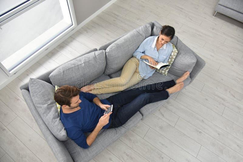 Övresikt av par som ligger på soffan royaltyfria bilder
