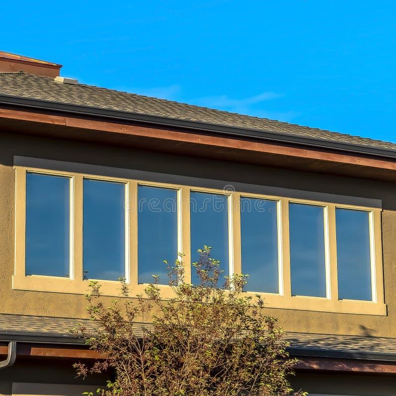 Övrevåning för fyrkantig ram av ett hus som fodras med rektangulära fönster mot klar blå himmel royaltyfri fotografi