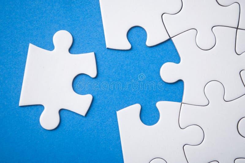 a última parte de enigma de serra de vaivém que falta no fundo azul para terminar a missão imagem de stock