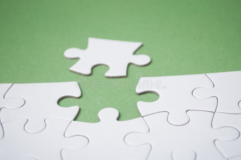 A última parte de enigma de serra de vaivém que falta no fundo verde para terminar a missão imagens de stock