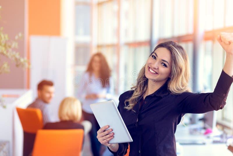 Únase a una era digital Mujer joven alegre que sostiene la tableta digital mientras que sus amigos que trabajan en fondo imagen de archivo