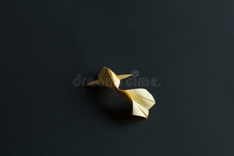 Única luz feito a mão do origâmi do ofício de papel - peixe amarelo da carpa do koi no fundo preto Vista traseira, colocação cent fotografia de stock