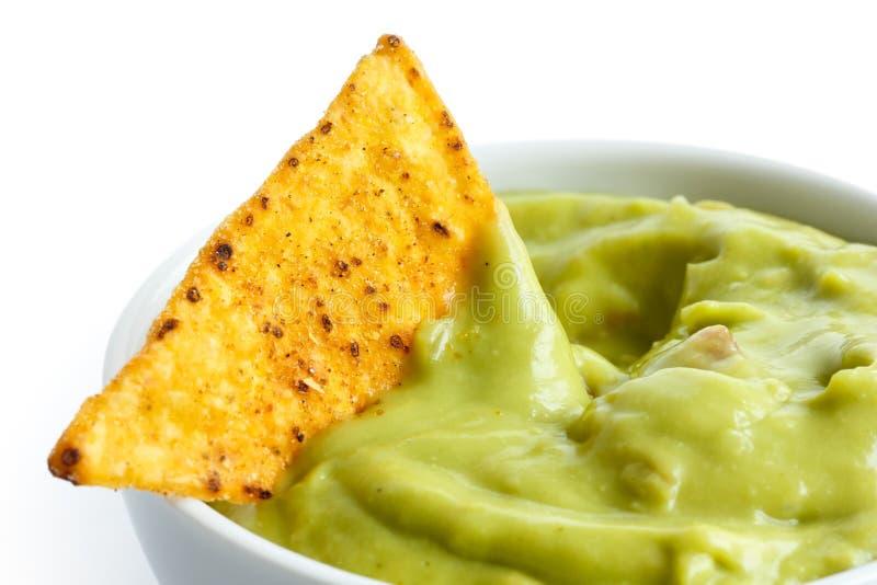 Única microplaqueta de tortilha na bacia de guacamole imagem de stock