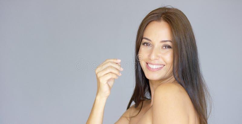 Única mulher adulta nova bonito com mão perto da cara imagem de stock royalty free