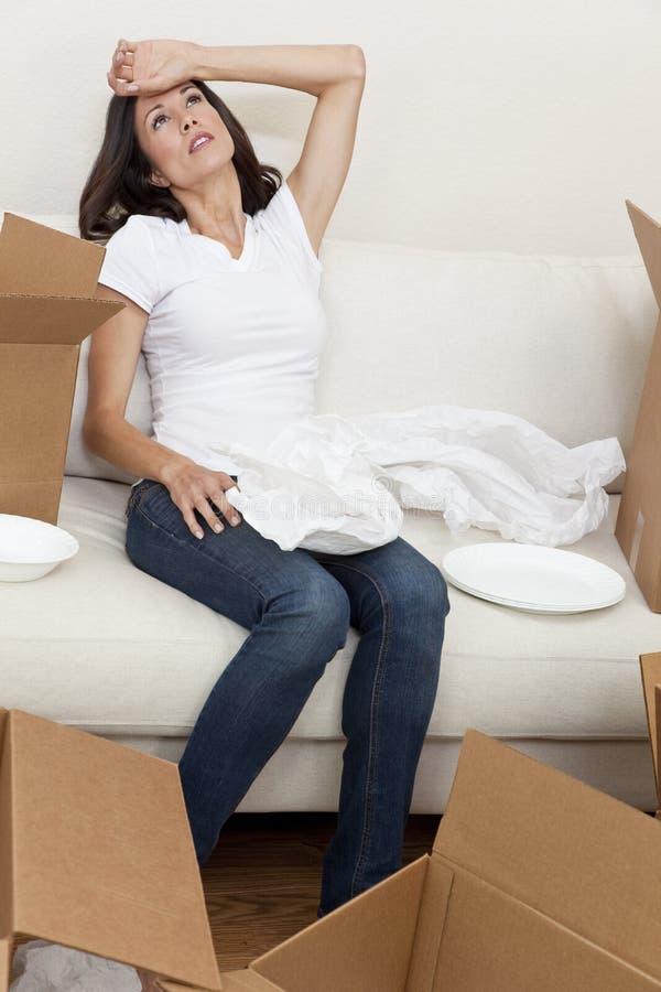 Única mulher cansada desembalando as caixas que movem a casa foto de stock